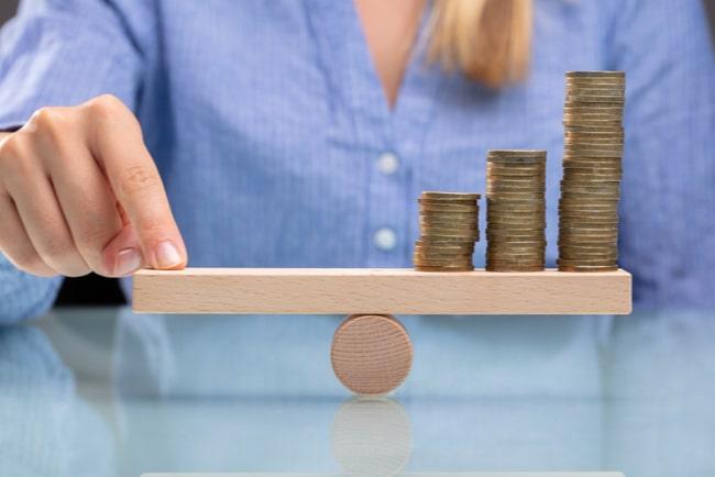 Affärskvinna balanserar högar med pengar med sitt finger