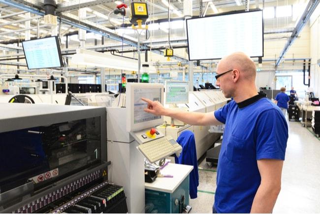 Man som strå i en högteknologisk fabrik och läser av data på en skärm
