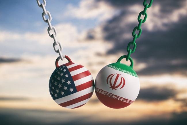Två rivningskulor med USA:s och Irans flagga som svingas mot varandra och krockar.
