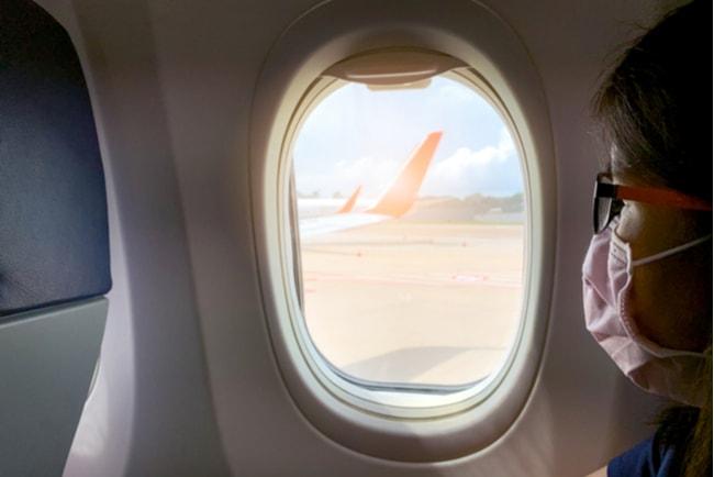 Sjuk asiatisk kvinna med munskydd tittar ut genom fönstret på ett flygplan