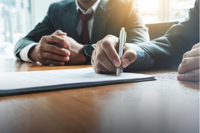 Två män i kostym sitter vid ett bord och skriver under ett avtal