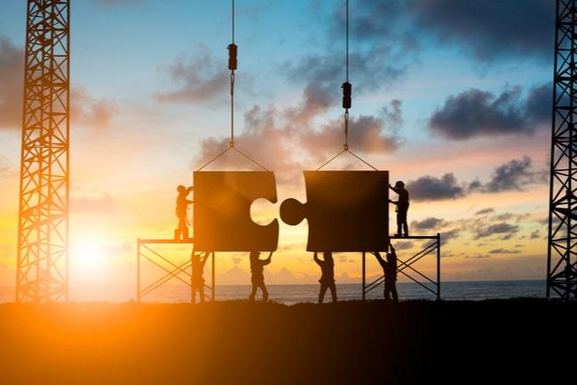 siluetter sätter samman stora pusselbitar med solnedgång i bakgrunden